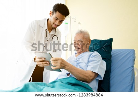 Asian Doctor is standing by explain the treatment information via the tablet to an elderly patient lying in bed in private sickroom. The treatment program is suitable for people to socialize elderly.