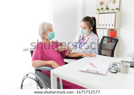 Asian doctor talk with old female patient about disease symptom, doctor use stethoscope listening lung of patient,   elderly health check up , they wear surgical mask on white background