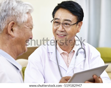 asian doctor talking to a senior patient, happy and smiling