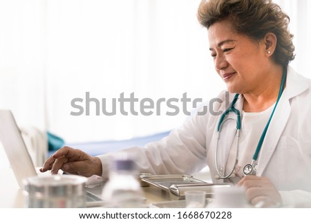 Asian doctor teleconferencing with patient in hospital room. Asian female doctor using computer researching medical data for hospital treatment in office. Physician working in hospital concept.
