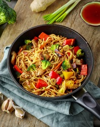 Asian egg noodles with vegetables and meat on cooking pan