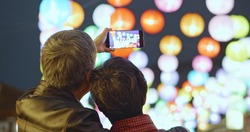 Asian elder couple visit lantern fesitival at night and take a video happily during chinese new year