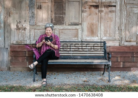 asian elder woman holding mobile phone in garden. elderly female texting message, using app with smartphone in park. senior use cellphone to connect with social network