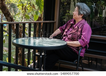 asian elder woman resting on terrace. elderly female relaxing on patio. senior leisure lifestyle at home