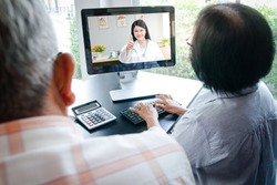 Asian elderly couples using computers Online video calling Talk to the doctor from home to inquire about health problems. Concept of social distance, hospital treatment