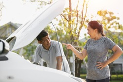 asian elderly husband and wife couples lose temper broken car have a problem on the road. man trying fix their car with woman scolding reproach.