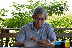 Asian elderly male wears gray shirt is using his taplet to surf the net and is chating, sending e-mails to his friend at home during the coronavirus spreading around the world at the moment.