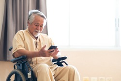 Asian elderly man patient holding mobile phone and conference call meeting to family while sitting on wheelchair at hospital