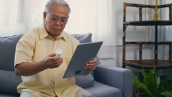 Asian elderly patient video call by digital tablet to doctor for inquire about which bottle of medication pills should be taken in living room at home,  Senior old man technology online healthcare