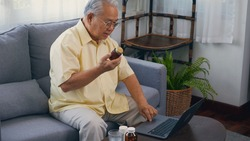 Asian elderly patient video call by laptop computer to doctor for inquire about which bottle of medication pills should be taken in living room at home,  Senior old man technology online healthcare