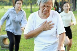 Asian elderly woman having difficulty breathing suffer from heart attack,heart problem while walking exercise at park, daughter and granddaughter are running to help,senior mother feeling chest pain