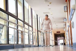 asian elderly woman walking using a walker in hall way of nursing home, low angle view.