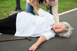 Asian elderly woman with walking stick on floor after falling down,assistant daughter help care to her,sick senior mother fell to the floor because of dizziness,faint,suffering from illness in park