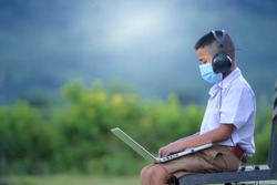 Asian elementary school-aged boys living in rural areas and schools in rural Thailand. Wear a mask to prevent the coronavirus (COVID 19) elementary school children online using a laptop to watch.