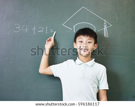 asian elementary school boy standing under a doctoral hat drawn with chalk on blackboard. Stock photo ©