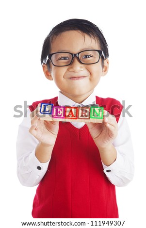 Asian elementary school student showing letter blocks spelling out LEARN. shot in studio isolated on white