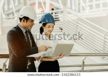 Asian engineer chief consult with secretary. Quality engineers or construction teamwork. Safety concern for engineering or building work site or plant. Wearing helmet and protective equipment can safe