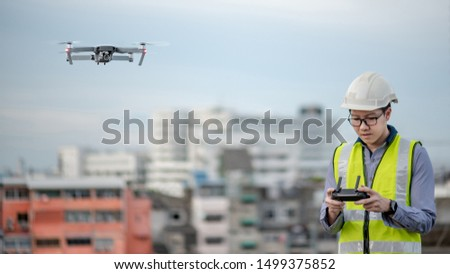 Asian engineer man flying drone over construction site. Male worker using unmanned aerial vehicle (UAV) for land and building site survey in civil engineering project.