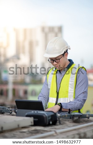 Asian engineer man working with drone, laptop and working tools at construction site. Male worker using unmanned aerial vehicle (UAV) for land and building site survey in civil engineering project.