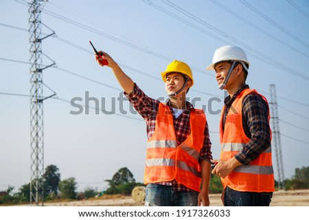 Asian engineer manager and foreman or leader discussion and pointing to construction site project on workplace and High voltage power line pylon in the background. Teamwork, Leadership concept. Foto stock ©