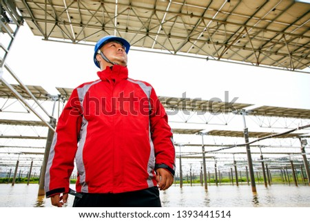 Asian engineer patrolling the lake photovoltaic area #1393441514