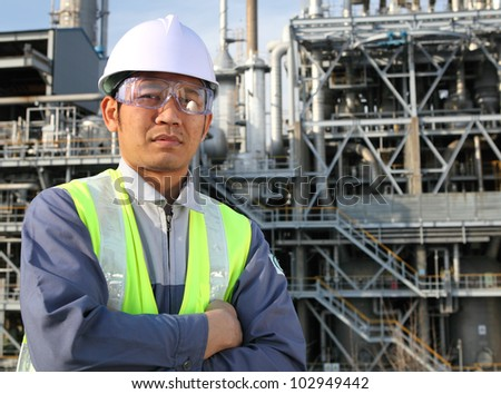 Asian engineer standing in front of a large oil refinery