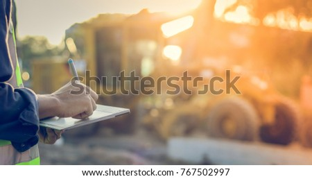 Asian engineer with hardhat using  tablet pc computer inspecting and working at construction site