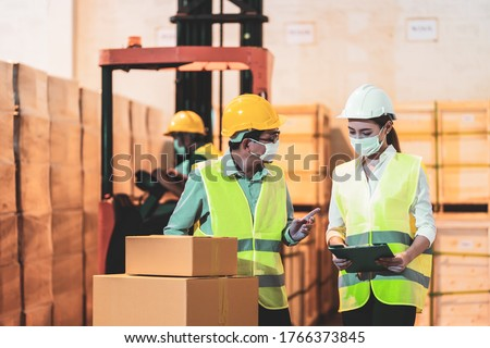 Asian engineers in uniform with helmet and face mask hold clipboard checking parcel box in warehouse with foreman in forklift. Concept of new normal work in logistic industry after Covid 19 outbreak