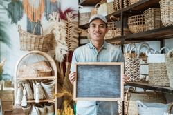 asian entrepreneur holding a blackboard standing in a handicraft shop with a handicraft background
