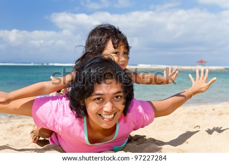 asian ethnic mother and child happy playing at the tropical beach