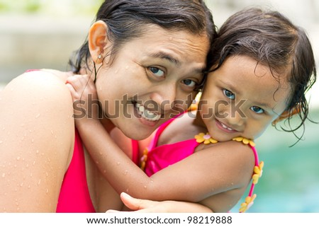 asian ethnic portrait of happy mother and little girl in swimsuit