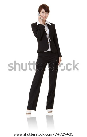 Asian executive woman talking on cellphone and smiling, full length portrait isolated on white background.