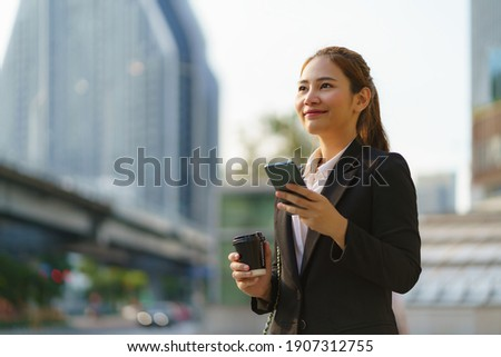 Asian executive working woman holding coffee cup and using a mobile phone in the street with office buildings in the background in Bangkok, Thailand.