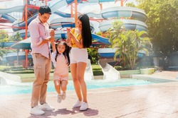 Asian families come to relax and travel to the outdoor water park. In the hot summer, bright sunlight helps each other to carry a mischievous daughter, walk around happily : Selective Focus