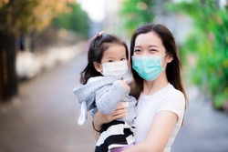 Asian family and adorable child girl wearing medical face masks on public roads. Mother and kid wear mask protection corona virus during outbreak pneumonia scourge. Face mask for protect pm2.5 dust.
