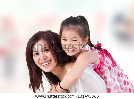 Asian family at home. Mother and child piggyback ride at indoor room.