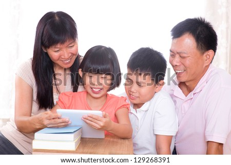 Asian family at home. Parents and children using digital tablet computer together.