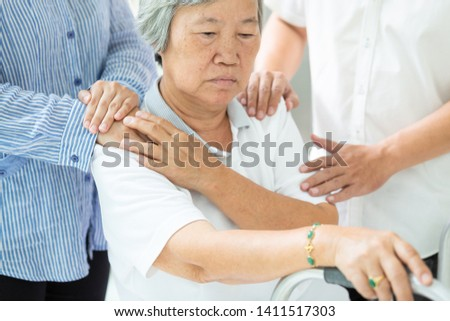 Asian family consoling depressed senior woman;sad elderly people with depressive symptoms need close care;hands on the shoulder;support
