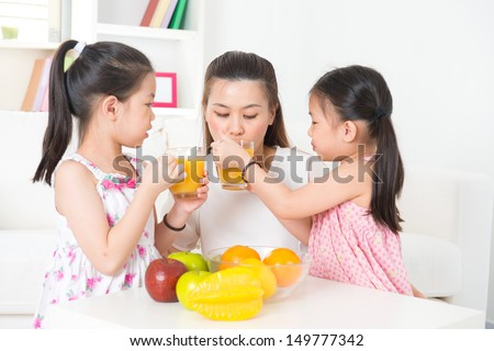 Asian family drinking orange juice. Happy Asian parent and children enjoying cup of fresh squeeze fruit juice at home.