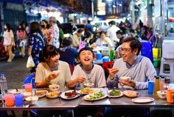 Asian family enjoy eating food on street food restaurant with crowd of people at Yaowarat road, Bangkok