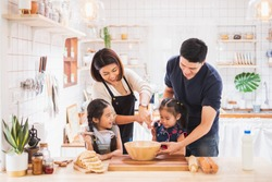 Asian family enjoy playing and cooking food in kitchen at home