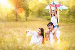 Asian family father, mother and daughter play ta kite in the outdoor park with sunrise and goldent colour, this image can use for family, relax, freedon, summer and travel concept