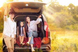 Asian family father, mother and daughter play togather in the Car in outdoor park with sunrise and goldent colour, this image can use for family, relax, freedon, summer and travel concept