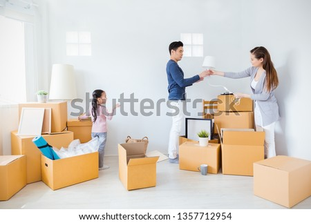 Asian family father mother daughter girl packing box moving to new house, online marketing e-commerce unpacking stuff belongings home delivery. Lifestyle happy asian family together relocation concept