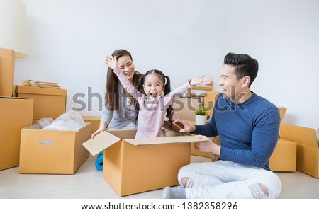 Asian family father mother daughter girl packing cardboard box relocation moving to new house, online marketing e-commerce unpacking stuff belongings home delivery. Lifestyle asian family together