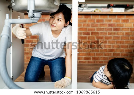 Asian family fixing kitchen sink