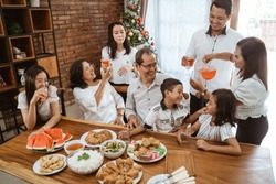 asian family fun having lunch with friends in diningroom together on christmas celebration