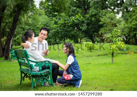 Asian family,husband holding hand comforting wife,father care mother depressive,alzheimer,child girl or daughter helping,support,depression woman patient,feel sad in outdoor park,health care concept