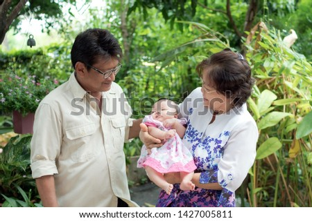 Asian family including grandmother, grandfather, and granddaughter. They are in the garden. Grandma and Grandma loves their grandchild. It is happy family day because their baby is 2 months.