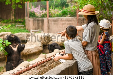 Photo of  Asian family kids learning outdoor on vacation summer holiday, mother brother and sisters looking bear show for feeding in zoo, boy child holding telescope , pen and notebook for writing knowledge